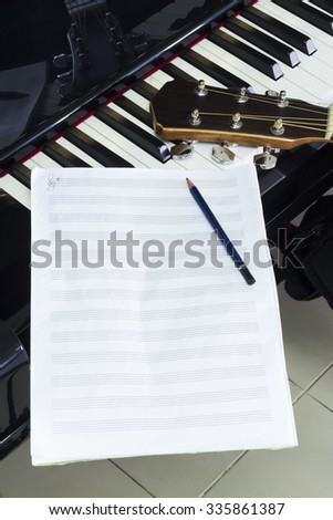 Staff Sheet and Pencil  with Guitar on Piano  - stock photo