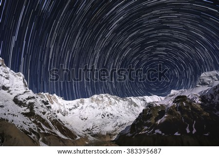 Star-trails over the snowy mountain peaks. Nepal, Annapurna region, Annapurna I from the Annapurna Base Camp. - stock photo