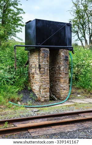 Steam Train Water Tower.  A water tank for refilling steam trains on the narrow gauge South Tynedale railway in Northern England. - stock photo