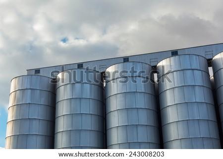 Steel grain silo towers.Set of storage tanks. - stock photo
