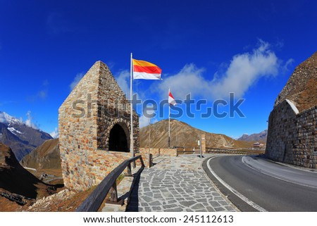 Steep turns are marked with red flags. Picturesque alpine road Grossgloknershtrasse. Bright sunny day. Photo taken by lens Fisheye - stock photo