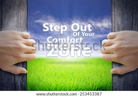 """""""Step out of your comfort zone"""" Motivational quotes. Hands opening a wooden door then found a texts floating among new world as green grass field, Blue sky and the Sunrise. - stock photo"""