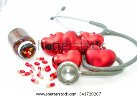 Stethoscope listening to a healthy red hearts  and  bottle with colorful pills - stock photo