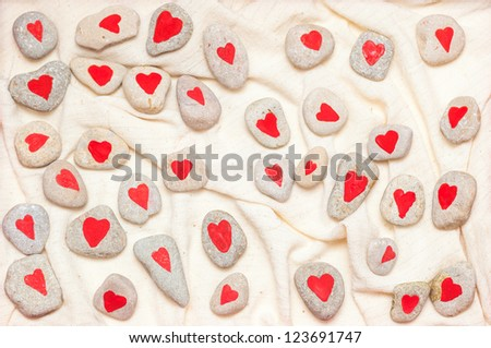 stones painted with red hearts on linen fabric - stock photo