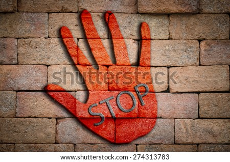 """ Stop "" on red hand on the brick wall. - stock photo"