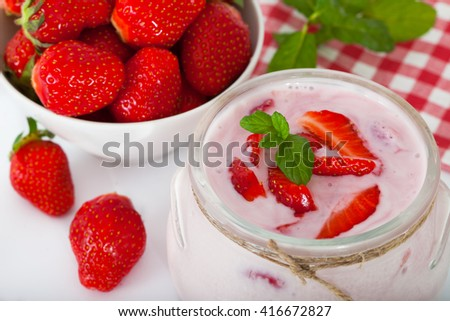 Strawberry flavored yogurt with fresh berries and min leaves over a white background - stock photo