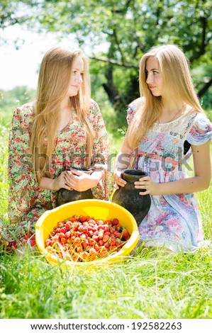 2 strawberry pickers: two happy young women teenage girl friends on farm gathering strawberry on bright summer day green outdoors background picture  - stock photo