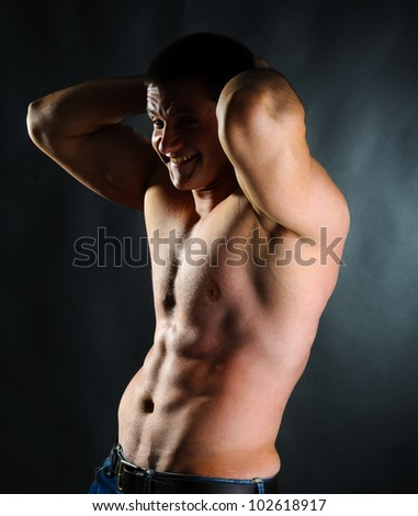 strong muscular athletic man on black background - stock photo