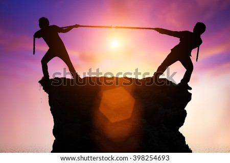struggle for defeat concept . Silhouette of playing tug of war of two men on a cliff. - stock photo