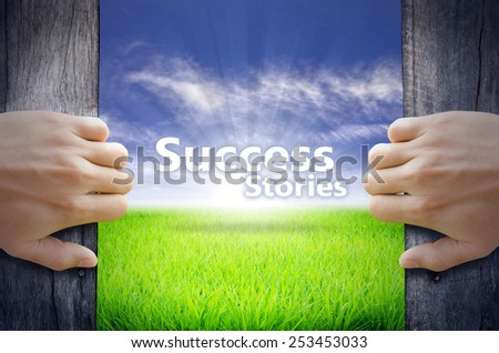 """""""Success story"""" Motivational quotes. Hands opening a wooden door then found a texts floating among new world as green grass field, Blue sky and the Sunrise. - stock photo"""