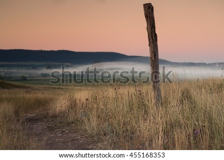 Summer field,road sign column with fog   - stock photo