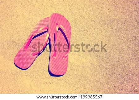 summer vacation background with a pair of sandals on a sandy beach done with a retro vintage instagram filter - stock photo