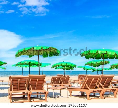 Sun loungers and a beach umbrella on beach - stock photo