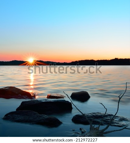 Sun star reflection on a shimmering lake with rocks in the foreground. - stock photo
