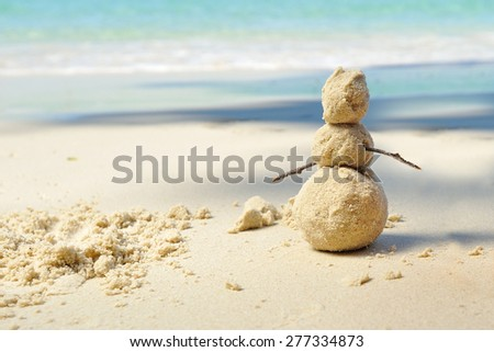 Sunny day on a tropical beach: snowman made of sand standing on the beautiful white sand coast and against on the background we can see the azure water of the sea - stock photo