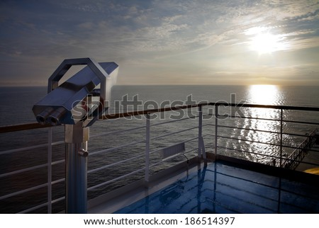 Sunrise at cruise deck ship and binoculars looking up. - stock photo