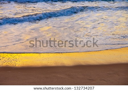 Sunset sea surf:  the foamy gentle surf crawling over the sand at the end of the day - stock photo