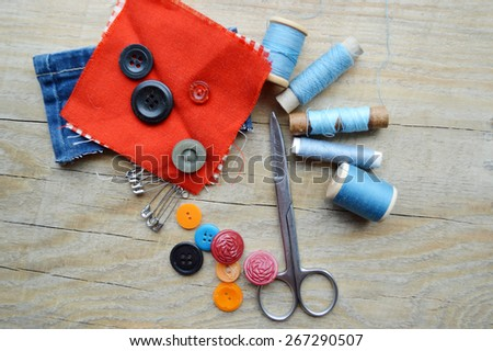 supplies and accessories for sewing on a light wooden table - stock photo
