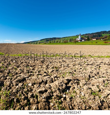 Swiss Village Surrounded by Forests and Plowed Fields - stock photo