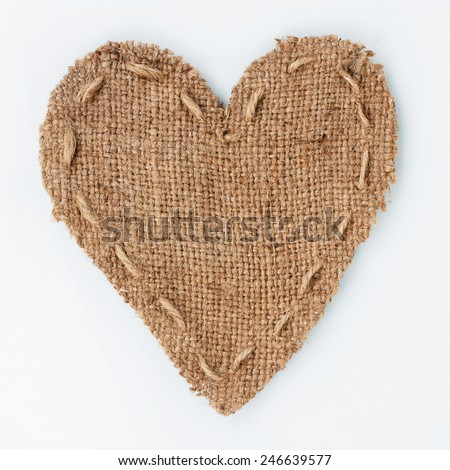 Symbolic heart of burlap lies on a white background, with place for your text - stock photo