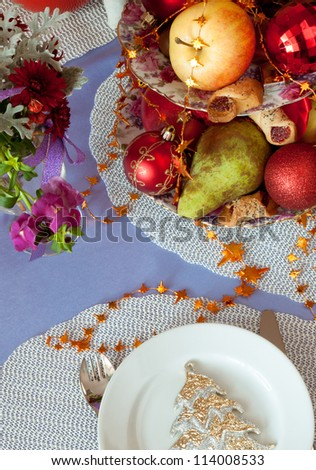 Table setting with Christmas decorations in gold and lilac - stock photo