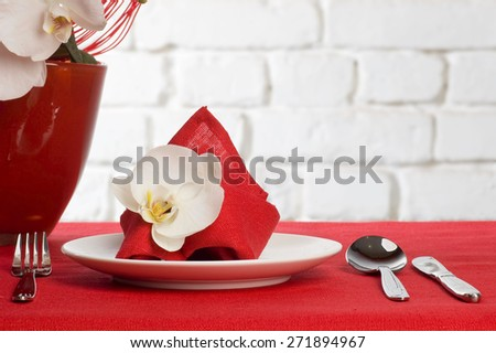 Table setting with white orchid flowers on red tablecloth on brick wall background - stock photo