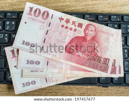 100 Taiwan Dollar bill on keyboard - stock photo