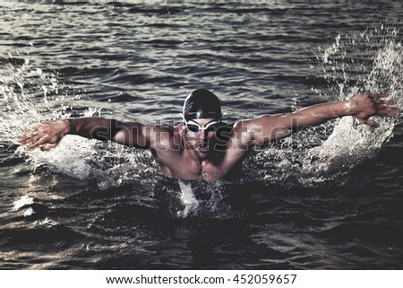 Taking breath swimming butterfly. - stock photo