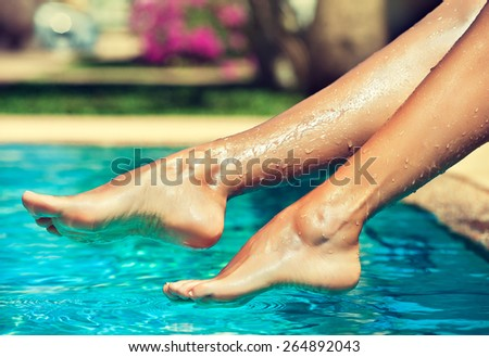 Tanned feet with pedicure compared to the pool and exotic nature - stock photo