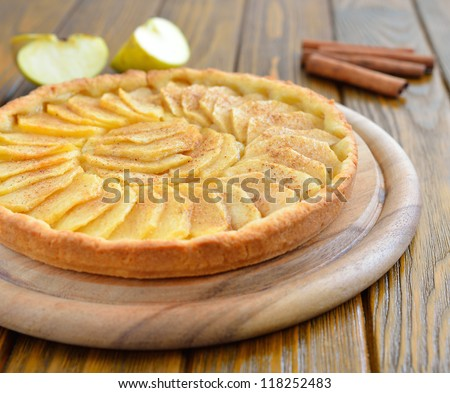 Tart with apples and cinnamon on a brown table - stock photo