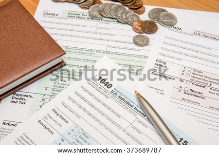1040 tax form with dollar, glasses, mouse, calculator, notepad - stock photo