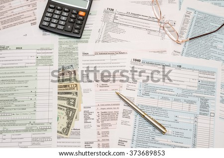 1040 tax form  with pen, dollar and calculator - stock photo