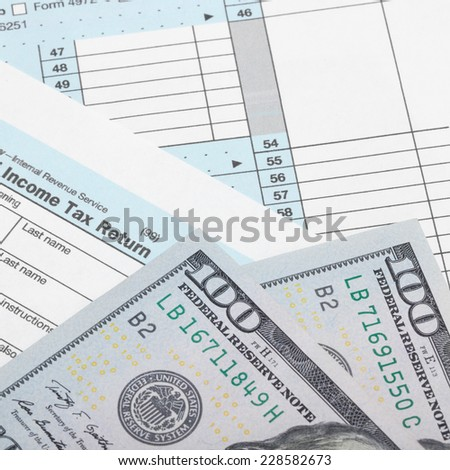 Tax Form 1040 with two 100 dollars banknotes - stock photo
