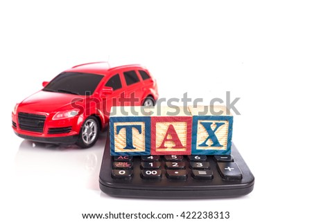 """TAX"" write in colorful wood alphabet blocks  with red model car and stack of coin isolated on white background - stock photo"