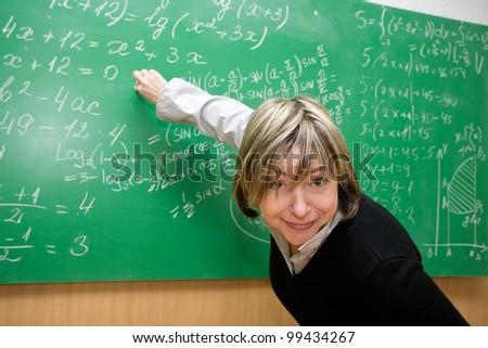 teacher is standing near blackboard in classroom - stock photo