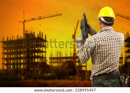 technician builder in protective safety equipment goggles hard hat with drill and tool belt working at high building construction site against beautiful sunset - stock photo