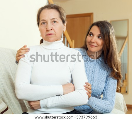 Teen girl asking for forgiveness from her mother after quarrel. Focus on mature woman - stock photo