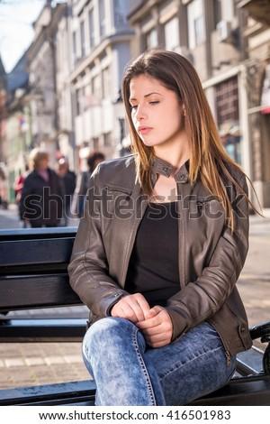 teen sad girl sitting on a bench, outdoor city street - stock photo