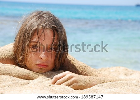 Teenager laying down on a beach, with the sea in the background. - stock photo
