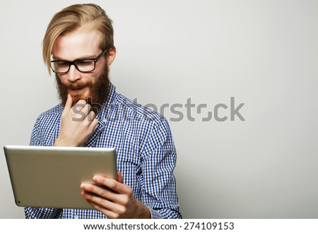 Tehnology, education and lifestyle concept: young man  using a tablet computer - over gray background - stock photo