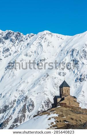 14th century Holy Trinity Church (Tsminda Sameba) near Mount Kazbek in Georgia - stock photo