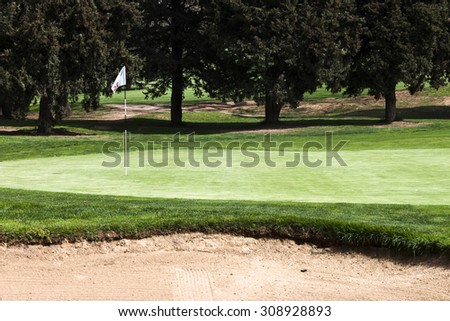 15 th hole flagstick on a putting green in a golf course. A bunker at the bottom. - stock photo