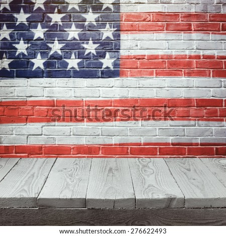 4th of july background with wooden table over USA flag painted on brick wall - stock photo