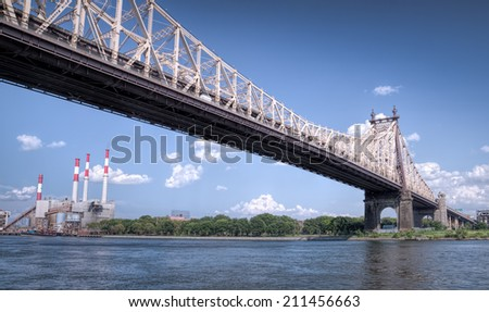 57th street bridge in NYC with cloudy blue sky and electric plant - stock photo