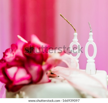 90th years old candles and cake in birthday party for the grandma, with pink background. - stock photo