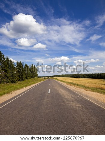 the asphalted road to summertime of year. along the road trees grow - stock photo