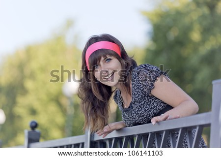The beautiful girl looks and smiles - stock photo