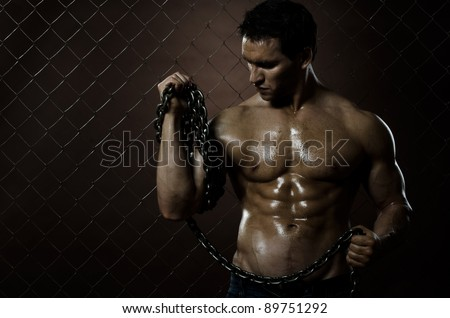 the beauty muscular worker  man,  with   chain in hands, on netting fence background - stock photo