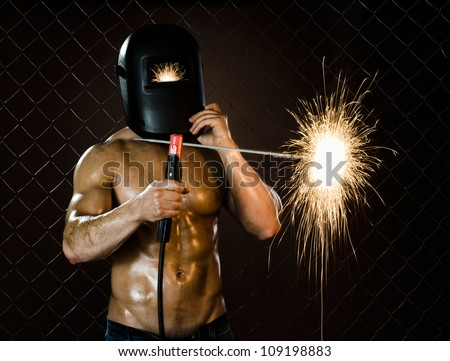 the beauty muscular worker welder  man, weld  electric arc-weld, on netting fence background - stock photo
