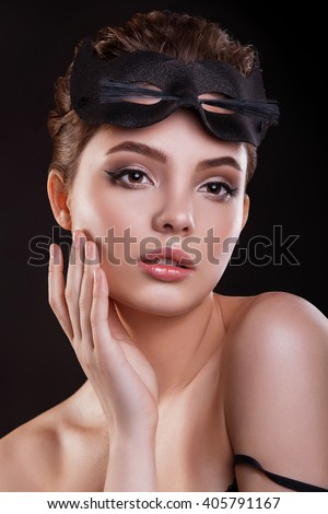 The beauty of the girl . Beautiful woman with mask of cat and professional makeup. Photographed in studio on a black background. - stock photo